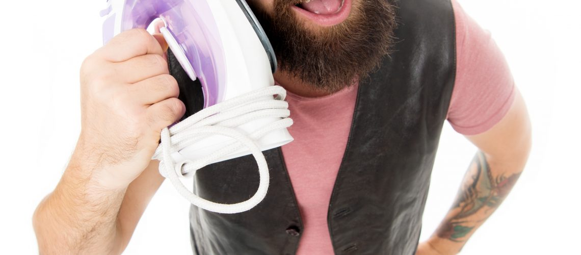 Man speaking iron as phone isolated white background. Wrong communication way. Bearded hipster use iron instead phone. Call household service. Mobile communication concept. Need more communication.